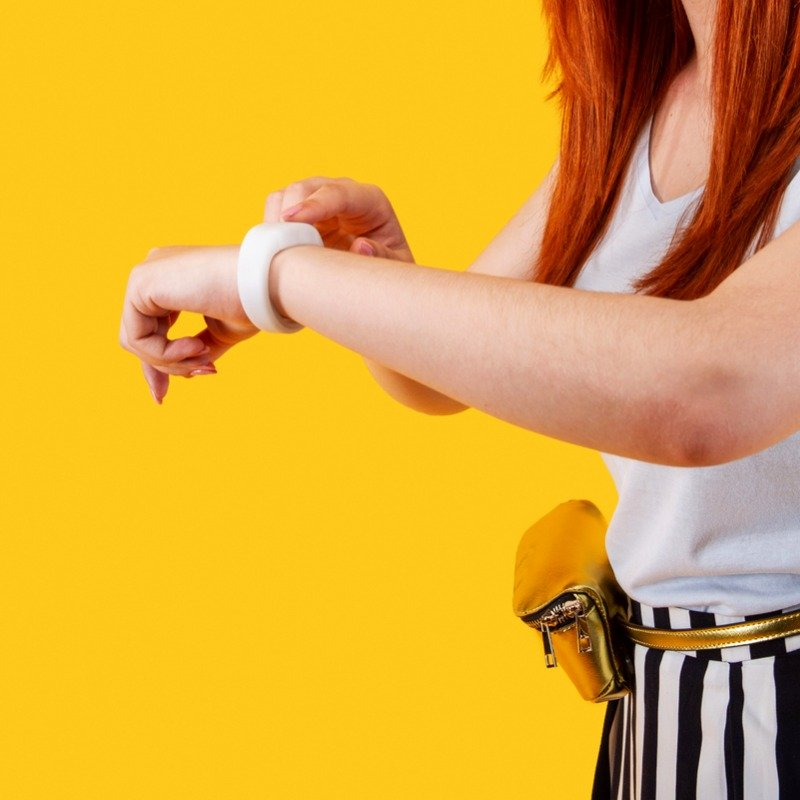 Yellow background with woman looking at wrist watch