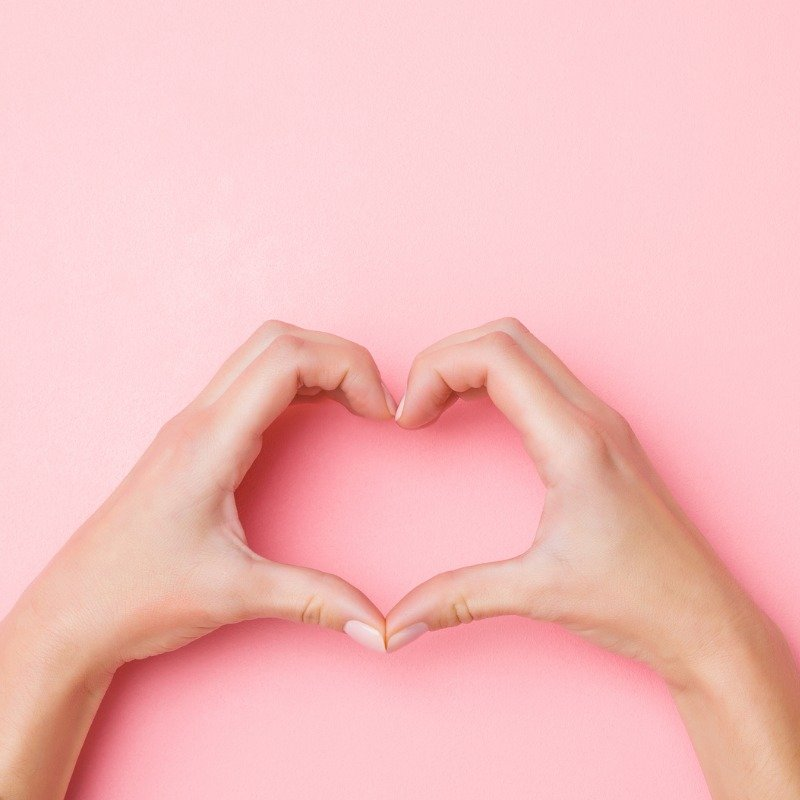 Pink background with hands forming heart shape