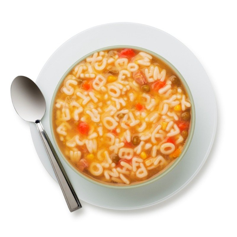 Alphabet soup in white bowl and spoon