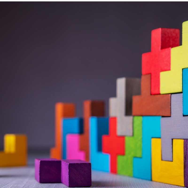 Brightly colored wodden blocks of different shapes on dark background