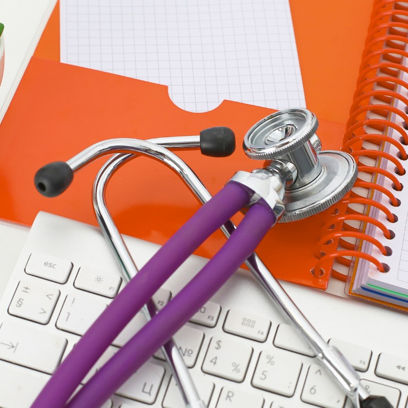 Keyboard, orange folder and purple stethoscope